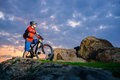 Cyclist Resting on Mountain Bike on the Spring Rocky Trail at Beautiful Sunset. Extreme Sports and Adventure Concept. Royalty Free Stock Photo