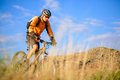 Cyclist riding the bike in the mountains on beautiful autumn mountain trail Royalty Free Stock Images