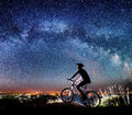 Cyclist riding bike in the night under starry sky Royalty Free Stock Photo