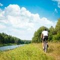 Cyclist Riding a Bike on River Bank Royalty Free Stock Photo