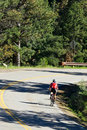Cyclist Riding Down Winding Road Stock Photos