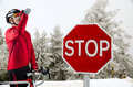 Cyclist on road bike near a stop sign in the mountains with snow Stock Photo