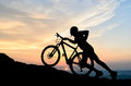 Cyclist in the sunset shadow of a climbing a hill while sun is setting on horizon Stock Images