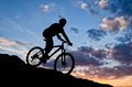 Cyclist in the sunset shadow of a going down a hill while sun is setting on horizon Royalty Free Stock Images
