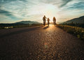 Cyclists family traveling on the road at sunset Royalty Free Stock Photo