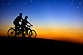 Cyclists at sunset silhouette of on hill Stock Images