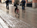 Cyclists on wet street in blurred motion with cobblestones Stock Images