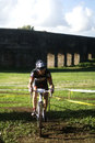 Cyclo cross competitor in action cycling through acquedotti cinecitta park rome italy Royalty Free Stock Photography