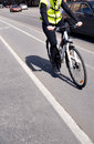 Cyslist cyclist on bicyce path by street with busy traffic Stock Images