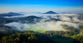 Czech typical summer landscape with fog. Hills and villages with foggy morning. Morning fall valley of Bohemian Switzerland park. Royalty Free Stock Photo