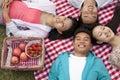 Cztery uśmiechniętego młodego przyjaciela z głowami dotyka i kłama na ich plecy ma pinkin w parku Obrazy Stock