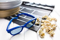 D glasses with clapperboard and popcorn on white wooden table Stock Image