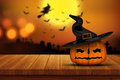 3D Halloween pumpkin on a wooden table with defocussed spooky im Royalty Free Stock Photo