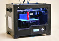 3D printer works and creates an object from the hot molten plastic