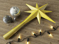 3d render of a gold decoration star and Christmas decoration baubles with black lights on a wooden background