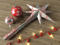 3d render of silver decoration star and Christmas decoration baubles with red lights on a wooden background