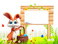 Easter bunny with big wooden sign and eggs basket