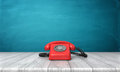 3d rendering of a bright red dial phone standing on a wooden desk and a blue wall background. Royalty Free Stock Photo