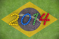D rendering of footballs form in to the year over a brazil flag painted on a grass field Stock Photography
