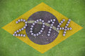 D rendering of footballs form in to the year over a painted grass field of brazil flag Royalty Free Stock Image