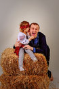 Dad and daughter in ethnic clothes in the manger on bales of hay says s ear laughed playfully shout Stock Photo