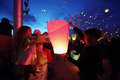 Dad and daughter with others launch lanterns into the night sky on a holiday Stock Photography