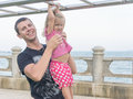 Dad and daughter playing promenade by the sea. young man, little girl hanging on the bar. Royalty Free Stock Photo