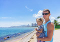 Dad and daughter playing on the promenade by the sea. young man, little girl Royalty Free Stock Photo