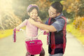 Dad fasten helmet on his daughter head young father helps to the while riding a bike the park Royalty Free Stock Image
