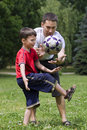Dad with his son playing football Stock Image