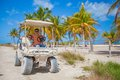 Dad with his two daughters driving golf cart at and tropical country Stock Image
