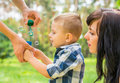 Dad holds his son`s hand and teaches him to blow soap bubbles. M Royalty Free Stock Photo
