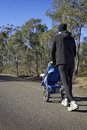 Dad jogging with baby stroller on a country road or walking Royalty Free Stock Image