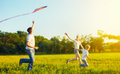 Dad, mom and son child flying a kite in summer nature Royalty Free Stock Photo