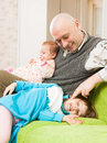 Dad plays with two daughters and sitting on couch Royalty Free Stock Photo