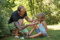 Dad puts antiseptic on sons elbow Royalty Free Stock Photo