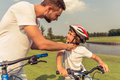 Dad and son cycling handsome young his cute little in casual clothes are riding bikes in park father is fastening his s helmet Royalty Free Stock Images