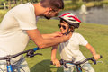 Dad and son cycling handsome young his cute little in casual clothes sun glasses are riding bikes in park father is fastening his Royalty Free Stock Photo