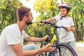 Dad and son cycling handsome young his cute little are riding bikes in park both are looking at each other smiling while father is Stock Photos