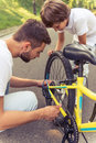 Dad and son cycling handsome young his cute little are riding bikes in park father is examining his s bicycle Royalty Free Stock Photography