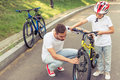 Dad and son cycling handsome young his cute little are riding bikes in park father is examining his s bicycle Stock Photography