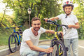 Dad and son cycling handsome young his cute little are riding bikes in park looking at camera smiling father is examining his s Royalty Free Stock Photography