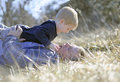 Dad and son playing wrestling a men his boy laying in the tall grass Stock Images