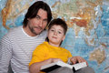 Dad and son reading  book on a map of the world Stock Images