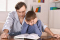 Dad and son reading a book portrait of father his sitting on sofa at home Royalty Free Stock Photo