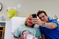 Dad taking picture of newborn and family in hospital Royalty Free Stock Photos