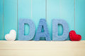 Dad text letters with hearts over blue wooden background white and red Stock Photography