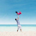 Dad throwing daughter in air at beach is his up the on the Royalty Free Stock Photo