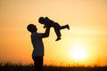 Dad throws the baby at sunset happy Royalty Free Stock Photo