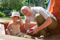 Dad with  toddler  playing with sand Stock Image